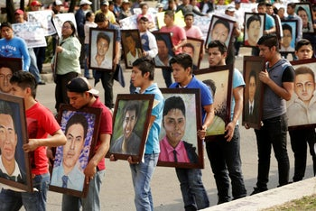 Relatives and activists hold paintings of some of the 43 missing students of Ayotzinapa College Raul Isidro Burgos during a protest to demand justice for the students, in Mexico City