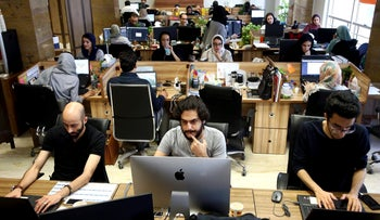 In this Monday, May 23, 2017, photo, staffers of the Snapp online taxi company work at their office in Tehran, Iran. Iran remains in many ways cut off economically from the rest of the world, fueling a surprisingly active local tech startup scene. Itג€™s driven by a growing number of Iranian millennials who see their country as a market ripe with opportunity. (AP Photo/Ebrahim Noroozi)