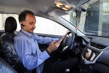 In this Monday, May 23, 2017, photo, Mostafa Meisami, driver of the Snapp online taxi company works with his smartphone at his car in Tehran, Iran. Iran remains in many ways cut off economically from the rest of the world, fueling a surprisingly active local tech startup scene. Itג€™s driven by a growing number of Iranian millennials who see their country as a market ripe with opportunity.