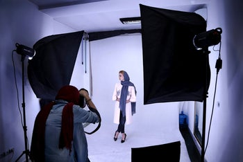 In this Sunday, May 22, 2017 photo, a photographer for the Bamilo online shopping site shoots a photo of a model wearing women's clothing to be featured for sale on their website, in Tehran, Iran. Iran remains in many ways cut off economically from the rest of the world, fueling a surprisingly active local tech startup scene. Itג€™s driven by a growing number of Iranian millennials who see their country as a market ripe with opportunity.