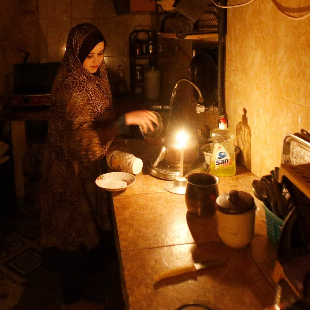 A Palestinian woman washes up in her kitchen during power cut at Shati refugee camp in Gaza City April 25, 2017. Picture taken April 25, 2017. REUTERS/Mohammed Salem