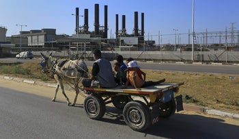A father and his children ride their donkey cart past the idled Gaza power plant at Nusseirat.