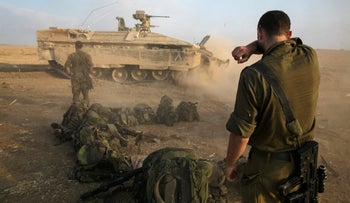 An Israeli soldier stands at a staging area after crossing back into Israel from Gaza, July 28, 2014.