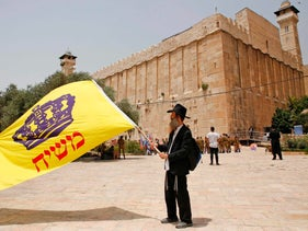 Israelis wave a flag printed with the word 'messiah' outside the Tomb of the Patriarchs in Hebron.