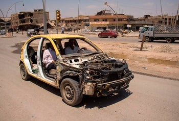 Iraqis driving a stripped-down car in west Mosul, July 12, 2017.