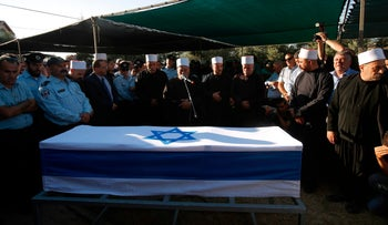 Members of the Druze community in Israel pray next to the coffin of Border Policeman Kamil Shnaan in the Druze village of Hurfeish, northern Israel, July 14, 2017.