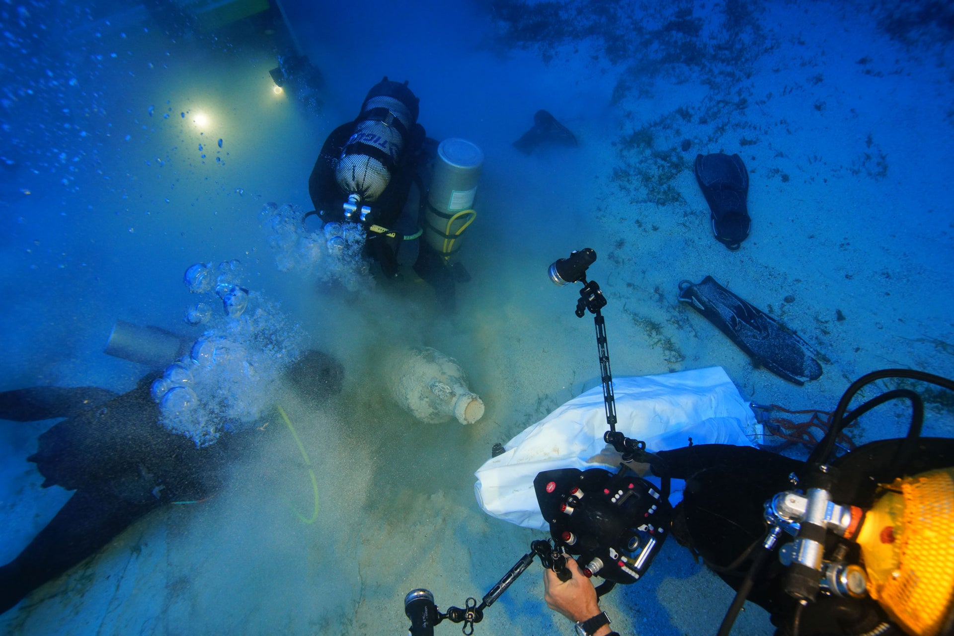 Archaeologists and the ROV robot clear sediment from a Roman North African amphora.