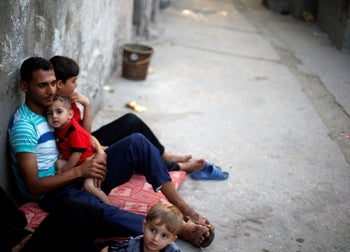 Palestinians sit outside their houses as they escape from the heat during power cut at Shati refugee camp in Gaza City, June 19, 2017