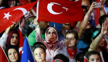 People wave Turkish flags at a ceremony marking the first anniversary of the attempted coup, Ankara,  July 16, 2017.