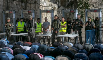 Israeli forces and Muslim worshipers at the entrance to the Temple Mount in Jerusalem's Old City, July 16, 2017.