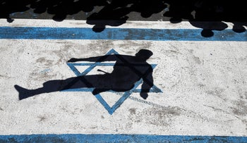 The shadow of a paramilitary Basij member is cast on the image of the Israeli flag during the Al-Quds (Jerusalem) Day in Tehran, Iran. June 23, 2017