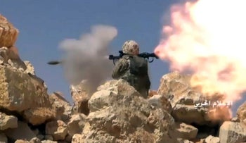 A screenshot provided by Syrian Central Military Media shows a Hezbollah fighter firing a rocket-propelled grenade during clashes with al-Qaida-linked militants on Lebanon-Syria border, July 22, 2017.