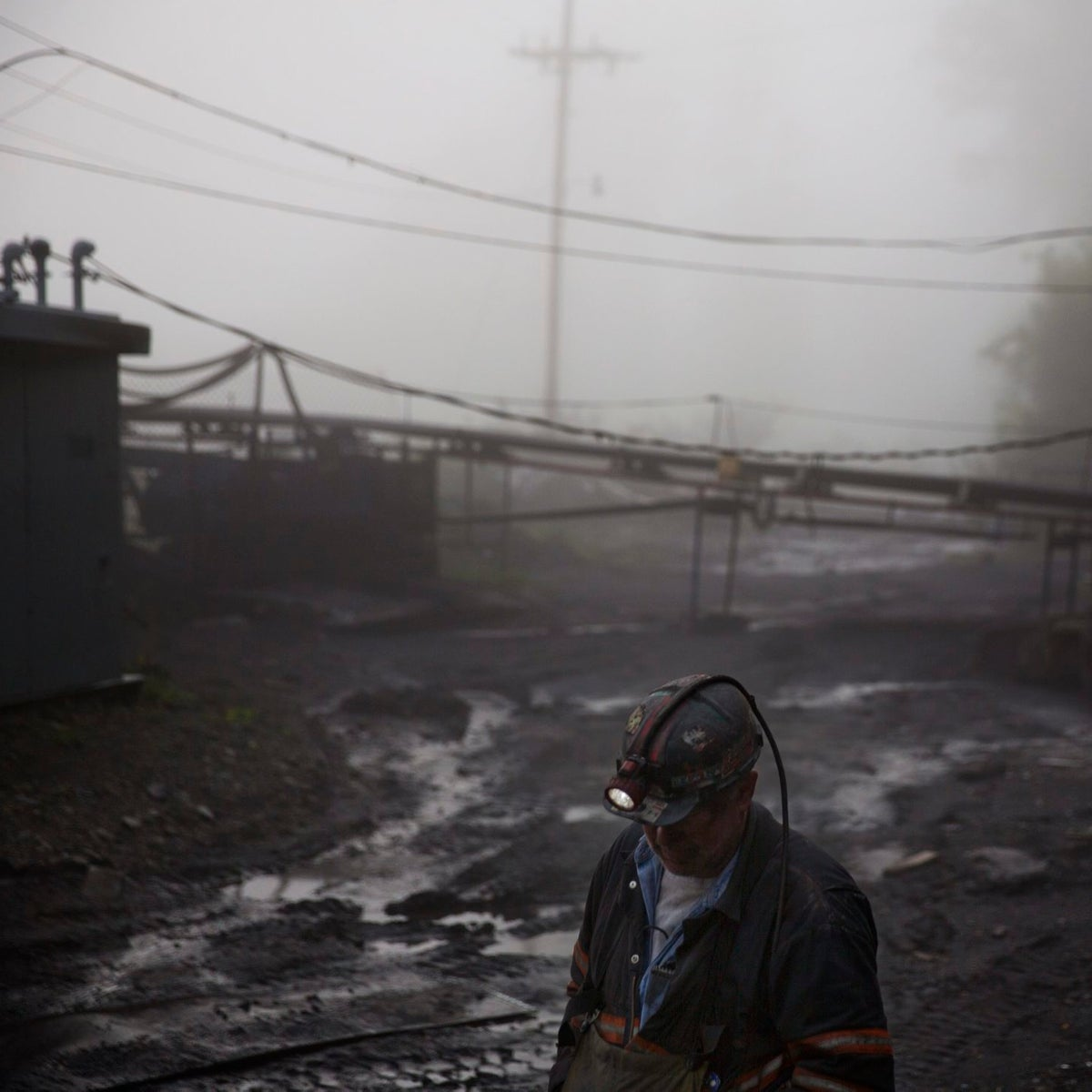 A coal miner walks through the morning fog before going underground in a mine less than 40-inches high in Welch.