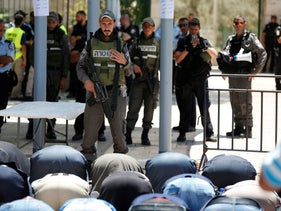Palestinians praying in front of Israeli policemen and newly installed metal detectors at an entrance to the Temple Mount in Jerusalem's Old City, July 16, 2017.