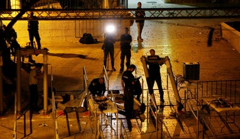 Dismantling the metal detectors at the entrances to the Temple Mount in Jerusalem Monday night.