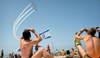 Israelis watch aircrafts during an air force flyover as part of 2009 Independence Day celebrations