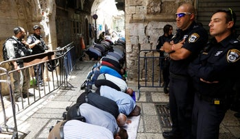 Palestinian men praying as Israeli security forces stand outside the compound known to Muslims as the Noble Sanctuary and to Jews as the Temple Mount, in Jerusalem's Old City, July 26, 2017.
