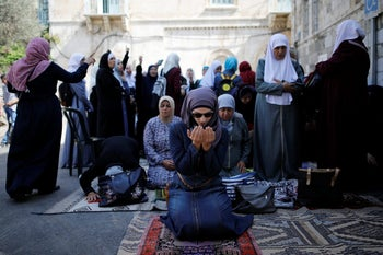 Palestinian women pray as others shout slogans outside the compound known to Muslims as Noble Sanctuary and to Jews as Temple Mount, in Jerusalem's Old City July 27, 2017.