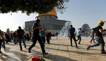 Palestinians react as a stun grenade explodes at the compound known to Muslims as Noble Sanctuary and to Jews as Temple Mount as Palestinians reentered the compound, July 27, 2017