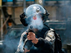An Israeli border guard fires a tear gas canister towards Palestinian protesters during clashes near the West Bank settlement of Beit El. July 24, 2017