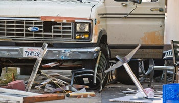 Broken restaurant tables and chairs are seen under a van that plowed into a group of people dining on a Los Angeles sidewalk injuring several Sunday, July 30, 2017.