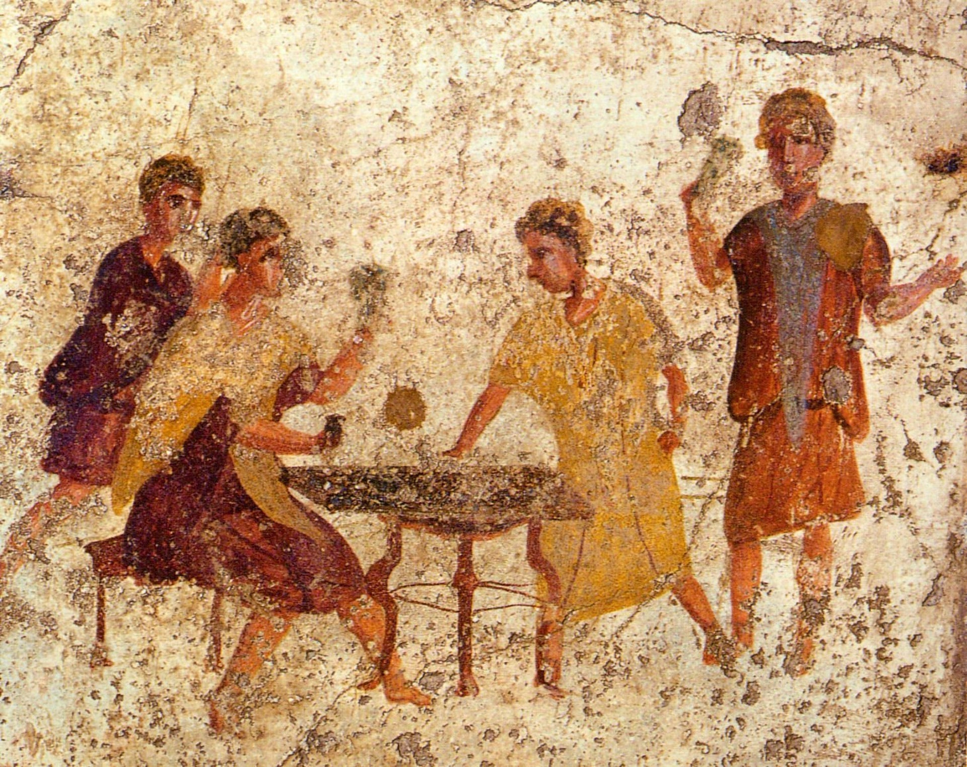 Gaming in ancient Pompeii: Ancient and rather tatty fresco shows four men, all seemingly wearing laurel leaves on their heads, playing a board game. Two of the men are garbed in dark red robes, one in a gold-colored robe and one in a dark orange robe. They seem to be barefoot.
