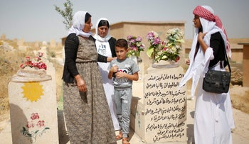 Yazidis visit a cemetery during a commemoration of the third anniversary of the Yazidi genocide in Sinjar region, Iraq August 3, 2017.