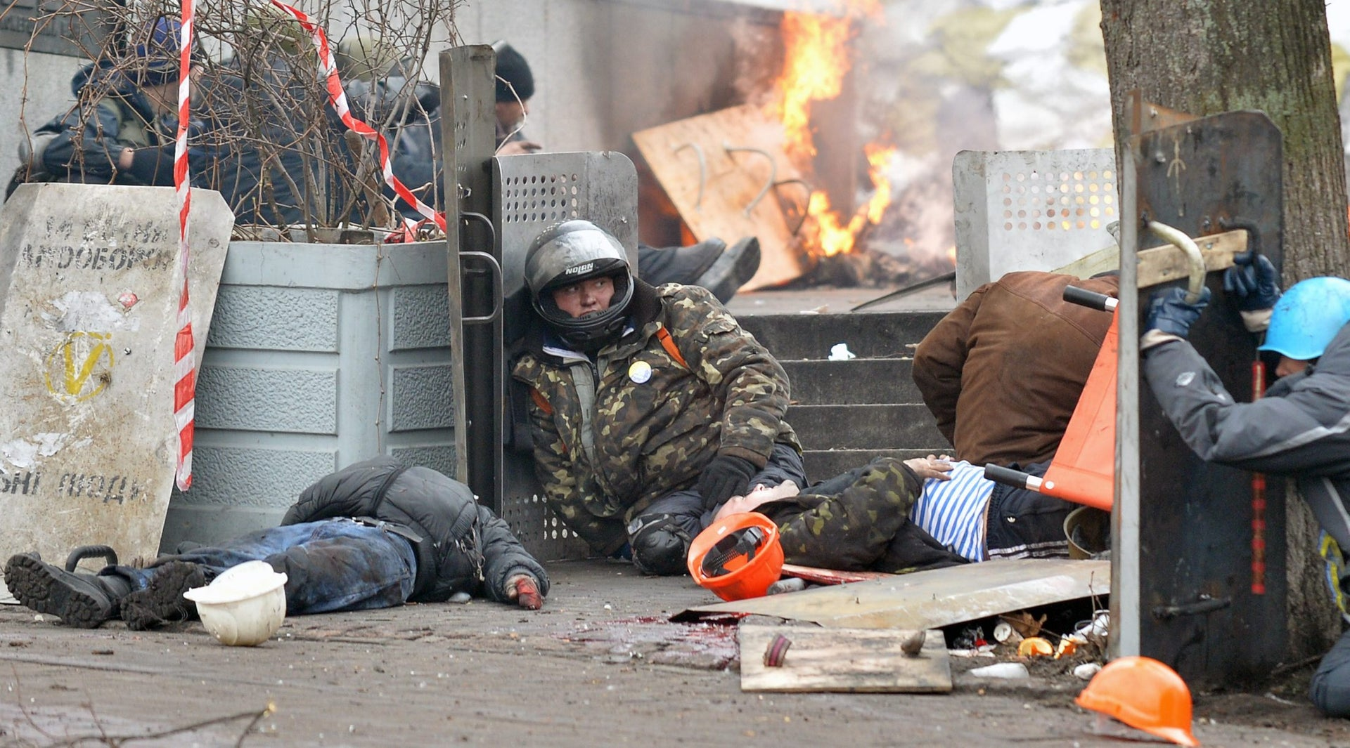 A wounded Maidan  activist next to the bodies of people killed by snipers during clashes between protesters and riot police in Kiev, Ukraine, February 20, 2014.