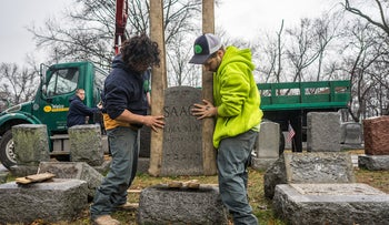 Workers placing headstones back on their bases at Chesed Shel Emeth Cemetery in the St. Louis area.