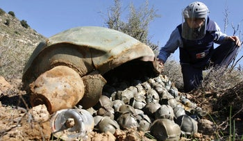 A researcher examines a cluster bomb that Israel fired on a village in Lebanon in 2006.