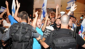 Right-wing protesters yell at their leftist opponents through police officers in Haifa during Operation Protective Edge, July 28, 2014.