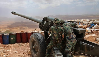 Lebanese army soldiers point a cannon at areas controlled by Islamic State group militants near Arsal, in northeast Lebanon on June 19, 2016.