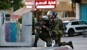 Israeli soldier aiming his weapon towards Palestinian protesters during clashes in the West Bank city of Bethlehem on July 19, 2017.