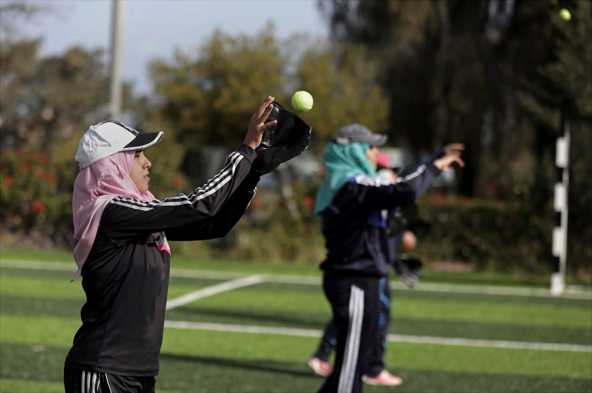 In this Sunday, March 19, 2017 photo, Palestinian women practice with tennis balls while training for an all women's baseball game, on a soccer field in Khan Younis, southern Gaza Strip. The female players wear hijabs, not helmets, toss around tennis balls, not baseballs and their leather gloves have been replaced by black imitations knitted from fabric. The group of young women are trying to bring baseball to Gaza -- giving the traditional American pastime a distinctly local feel.