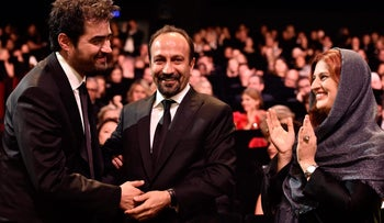 Iranian actor Shahab Hosseini, left, celebrating with director Asghar Farhadi, center, after being awarded the best actor prize at the 69th Cannes Film Festival in France, May 22, 2016.