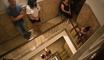 People take cover inside their building staircase during an air raid siren warning of a rocket attack in Tel Aviv, July 12, 2014.