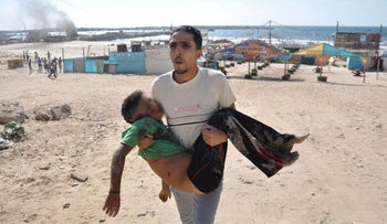 A Palestinian man carries the body of a boy,who was killed by a shell fired by an Israeli naval gunboat,on a beach in Gaza City July 16, 2014.