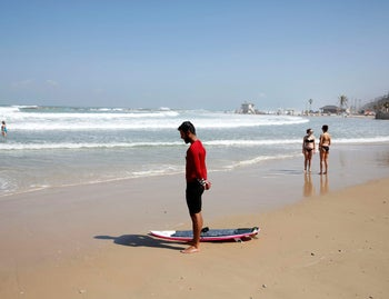Beach-goers stand still as a two-minute siren marking annual Holocaust Remembrance Day in Israel is sounded in Netanya, Israel May 5, 2016.