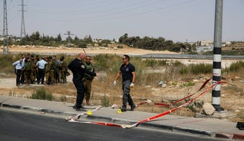 Israeli police officers inspect the scene of an attack at the Gush Etzion junction in the West Bank, Friday, July 28, 2017.