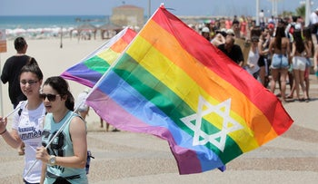 An illustrative photo showing women holding rainbow flags with the Star of David on them at a gay pride parade in Tel Aviv.