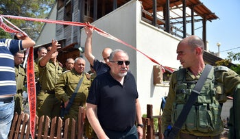 Defense Minister Lieberman, center, at the scene of attack in Halamish