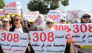 Women activists protest in front Jordan's parliament in Amman on Tuesday, August 1, 2017 with banners calling on legislators to repeal a provision that allows a rapist to escape punishment if he marries his victim.