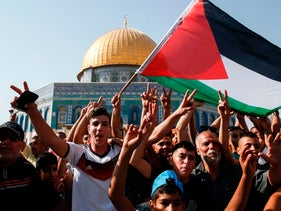 Palestinian Muslims wave a national flag and flash the victory sign in front of the Dome of the Rock in the Haram al-Sharif compound, or Temple Mount, in the old city of Jerusalem. July 27, 2017