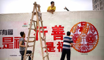 """Workers put up a propaganda billboard outside of a construction site in Beijing, Wednesday July 26, 2017. The characters at center read """"Doing good deeds is a blessing."""""""