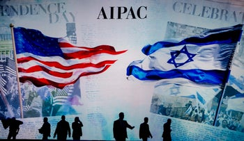 The silhouettes of workers are seen adjusting the stage before the start of the plenary session of the American Israel Public Affairs Committee policy conference in Washington, D.C., March 2, 2015.