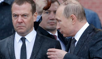 Russian President Vladimir Putin (R) speaks with Prime Minister Dmitry Medvedev in the rain during a wreath-laying ceremony marking the anniversary of the Nazi German invasion in 1941, by the Kremlin wall in Moscow, Russia June 22, 2017.