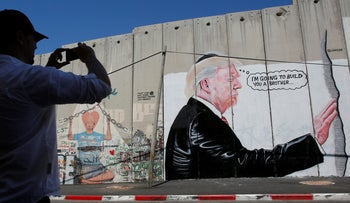 A man takes a photo of a graffiti depicting U.S President Donald Trump on the controversial Israeli barrier in the West Bank town of Bethlehem August 4, 2017.