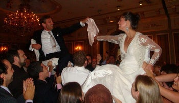 Aja and Evan Cohen are lifted in chairs at their wedding.