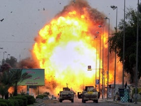 """A car bomb explodes, detonated by U.S. troops after it was discovered at the scene of the double car bombing in Baghdad, Iraq Thursday, April 14, 2005. The initial attack killed 18 and wounded three dozen, but no one was injured in this controlled explosion. The sign at left reads """"Keep Your City Clean"""" in Arabic."""