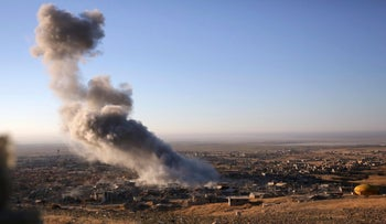 In this Thursday, Nov. 12, 2015, file photo, smoke believed to be from an airstrike billows over the northern Iraqi town of Sinjar. The Islamic State militants who stormed into the Iraqi town of Sinjar in 2014, massacring members of the Yazidi minority and forcing women into sexual slavery, are gone.